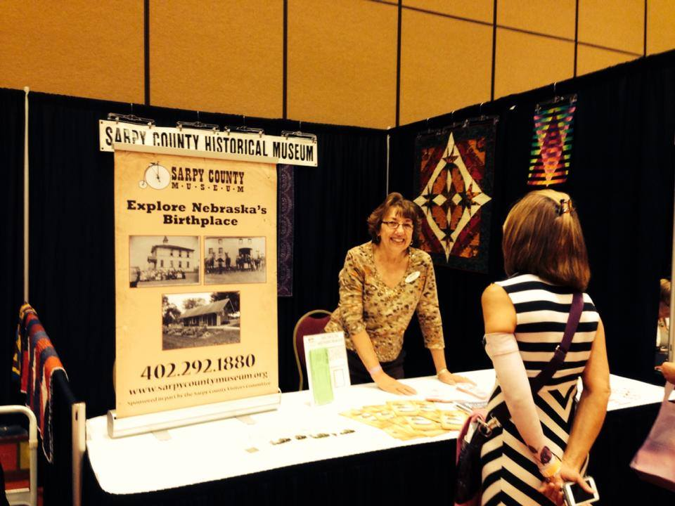 Volunteer Emily Larson helps with our booth at the Omaha Quilt Guild Show.